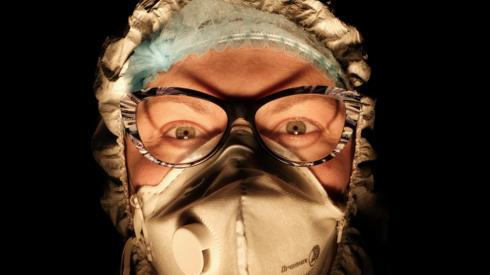 A female nurse wearing a face mask with a dark background behind her
