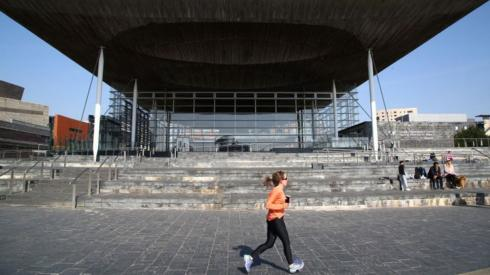 A woman jogging in front of the Senedd