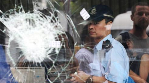 Hong Kong police officer seen through shattered glass