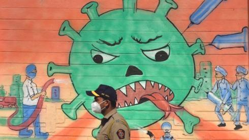 A policeman walks past a mural of frontline warriors attacking the gigantic coronavirus,
