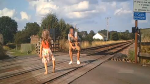 Man taking a photo of a girl on a level crossing