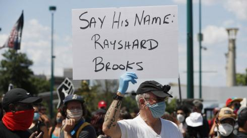 A protester holds a sign with Rayshard Brooks' name in Atlanta
