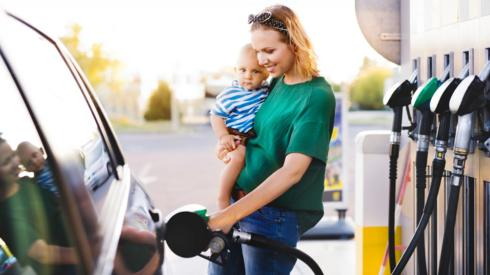 Mother holding baby at petrol pump