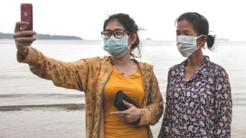 Two women in masks take a selfie on a beach