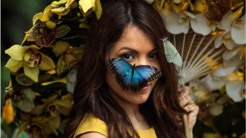 A Blue Morpho butterfly sits on the face of model Jessie Baker as she poses during a photocall at RHS Garden Wisley