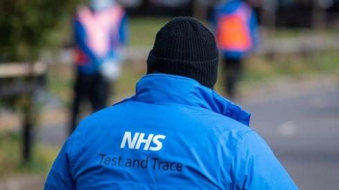 """An NHS Test and Trace logo on a member of staff""""s jacket"""