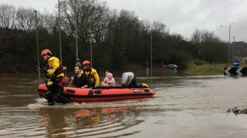 People being helped to safety in a boat in Nantgarw