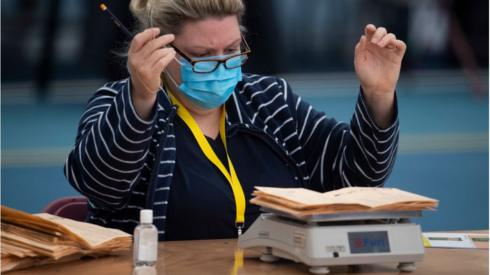 A woman reacts as votes are weighed during the Senedd election count at the Cardiff House of Sport