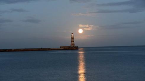 The sun setting over Roker Pier and Lighthouse in Sunderland