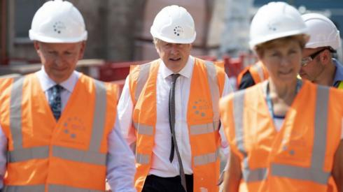 Boris Johnson wearing hi-vis and hard hat flanked by two others wearing the same.