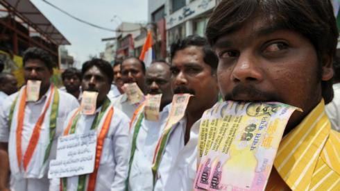Supporters of Indian social activist Anna Hazare, including members of the Telugu Desam Party (TDP), pose with fake rupee notes signifying corruption during a rally in Hyderabad on August 17, 2011.