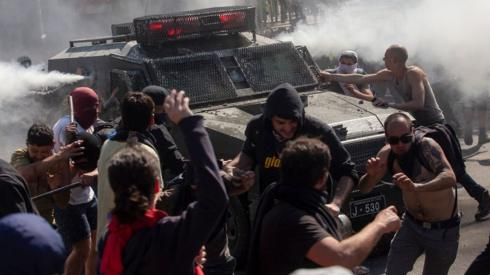Demonstrators clash with a riot police vehicle during protests in Santiago