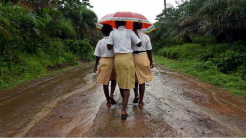 Three schoolgirls walks home in a countryside village of Sierra Leone on 12 July 2019.