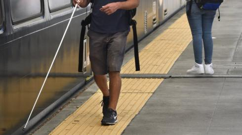 Visually impaired person with a stick next to a train