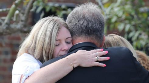 Pc Harper's mother hugs other family members