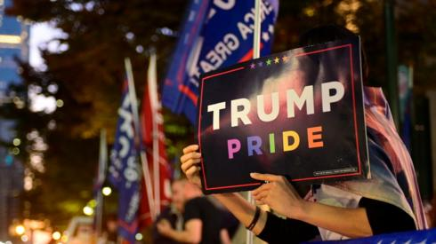 "A supporter of U.S. President Donald Trump holds up a ""Trump Pride"" sign during a rally outside the Pennsylvania Convention Center six days after the election in Philadelphia, Pennsylvania, U.S. November 9, 2020."