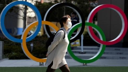 Woman in mask walks past Olympic rings