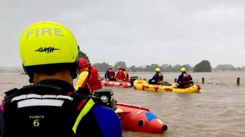 A fire and rescue response team on rescue kayaks during the NSW floods