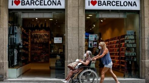 A woman pushes a wheelchair in downtown in Barcelona
