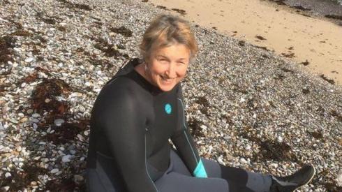 Rhiannon ar y traeth mewn wetsuit
