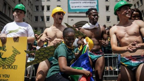 Springbok supporters wear South African flag speedos to mimic Springbok scrumhalf Faf de Klerk attire on the winning night of the Rugby World Cup during a parade through the streets of Johannesburg CBD on an open top bus while showing the Web Ellis trophy on November 7, 2019 in Johannesburg, South Africa.