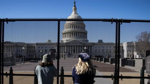 People view the U.S. Capitol, behind security fencing