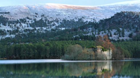 A castle reflecting in the loch with a snowy hill behind it.