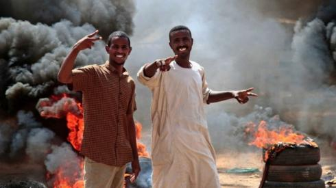 Sudanese demonstrators flash victory signs by a roadblock made of buring tyres in the capital Khartoum, on October 26, 2021, as they protest a military coup that overthrew the transition to civilian rule