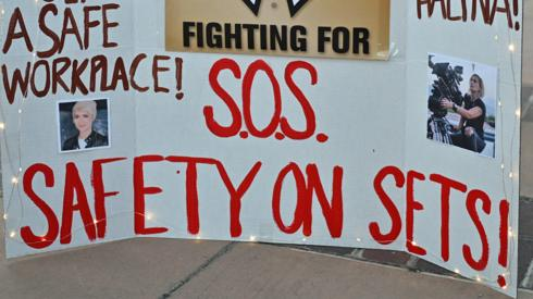 """Vigil for Halyna Hutchins with people holding up placards calling for """"safety on set"""""""