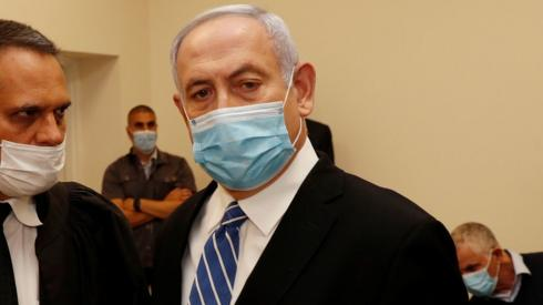 Israeli Prime Minister Benjamin Netanyahu, wearing a mask, stands inside the courtroom as his corruption trial opens on 24 May 2020