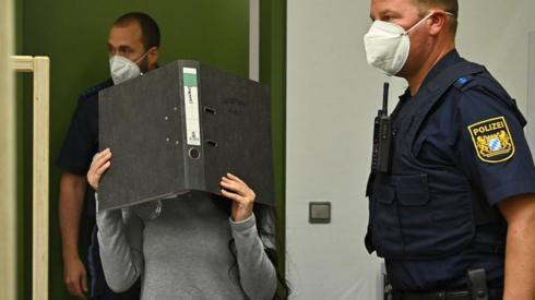 Jennifer Wenisch in court, covering her face with a folder, 13 Oct 21