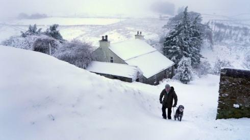 A dog walker negotiates heavy overnight snow in Carrshield in the Pennines, near Hexham in Northumberland