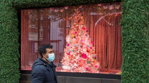 A man wearing a face mask passes a Christmas window display on Oxford Street,