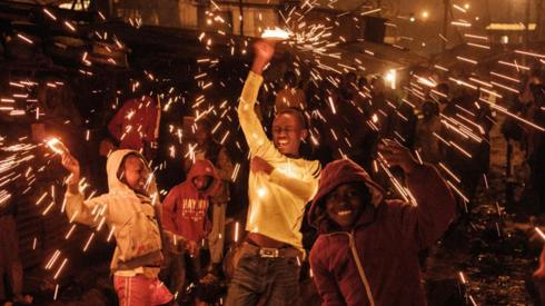 Children spin burning steelwools to sprinkle fire sparks as they celebrate the new year on a street of Kibera slum in Nairobi, on January 1, 2020.