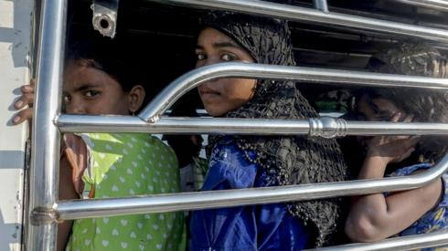 Women and children seen in a police vehicle after trying to flee (file photograph)