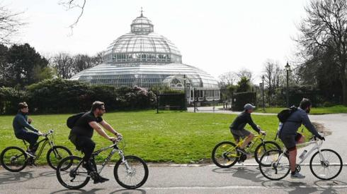 People cycle past Victorian Palm House in Sefton Park