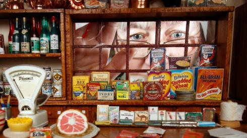 A woman looks through the window of a miniature shop that is filled with miniature products