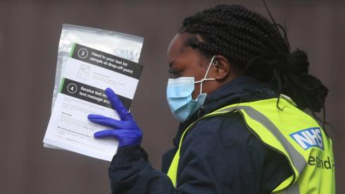 An NHS Test and Trace worker, holds self test kits at a testing centre in Bolton