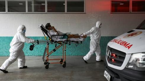 Health workers transport Joao Oliveira, 77, who, according to his wife, is suffering with COVID-19 symptoms, at 28 de Agosto hospital