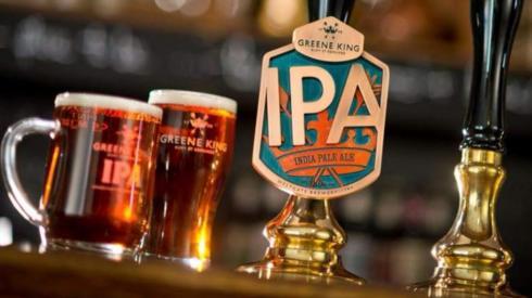 Greene King beer pump and glasses of beer.