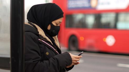 A woman wearing a protective mask uses her mobile at a bus stop