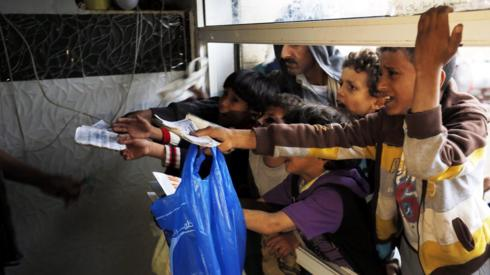 "people wait to get their families"" free food ration from a charity kitchen in Sanaa"
