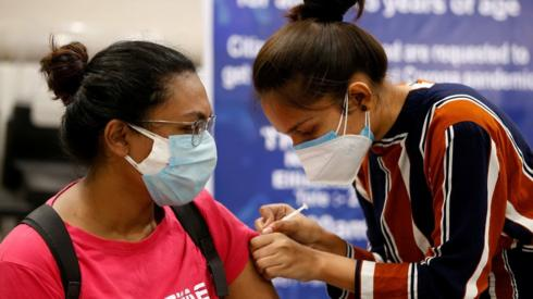 A woman receives a dose of COVISHIELD, a coronavirus disease (COVID-19) vaccine manufactured by Serum Institute of India, at a vaccination centre in Ahmedabad, India, May 1, 2021