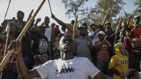 Zulu residents of the Jeppe Men Hostel scream waving batons in the Johannesburg CBD on September 3, 2019