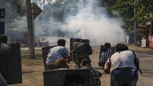 Protesters react after police fire teargas in Mandalay, Muanmar. Photo: 13 March 2021