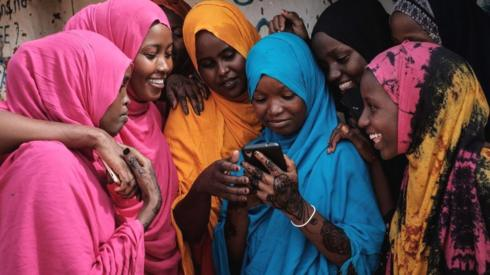 Young Somali refugee women look at a phone as they stand together at Dadaab refugee complex, in the north-east of Kenya - 2018