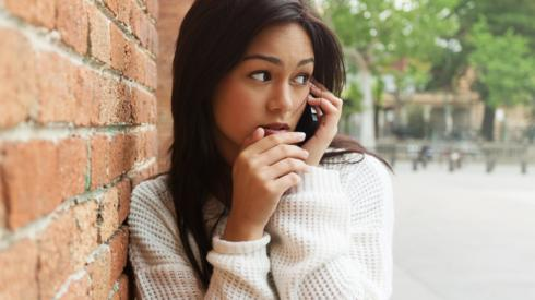 Staged picture of woman looking worried on smartphone