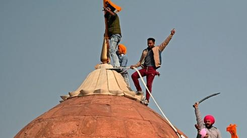 Protesters climb on a dome at the ramparts of the Red Fort in Delhi
