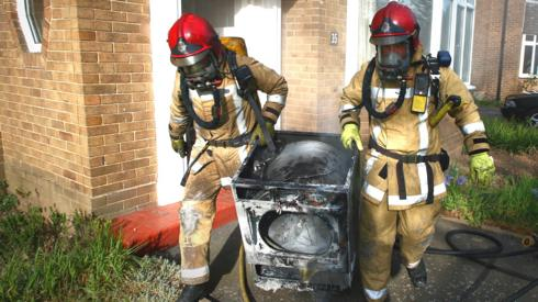 Two firefighters carrying a fire-damaged tumble dryer from a house fire