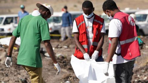 Forensics investigators and recovery teams collect personal effects and other materials from the crash site of Ethiopian Airlines Flight ET 302